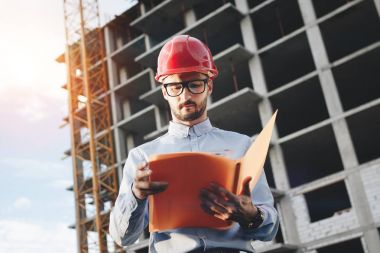 Young bearded engineer in red construction helmet on background of a building under construction with drawings and a folder in his hands