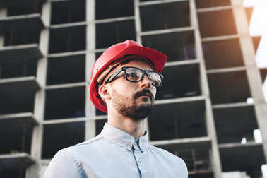 Young successful businessman builder with glasses and red hard hat on construction site inspects construction of new modern factory