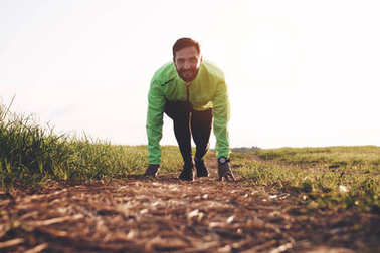 Sportsman in running start pose on field. Athlete in sportwear and smartwatch is being prepared start run training