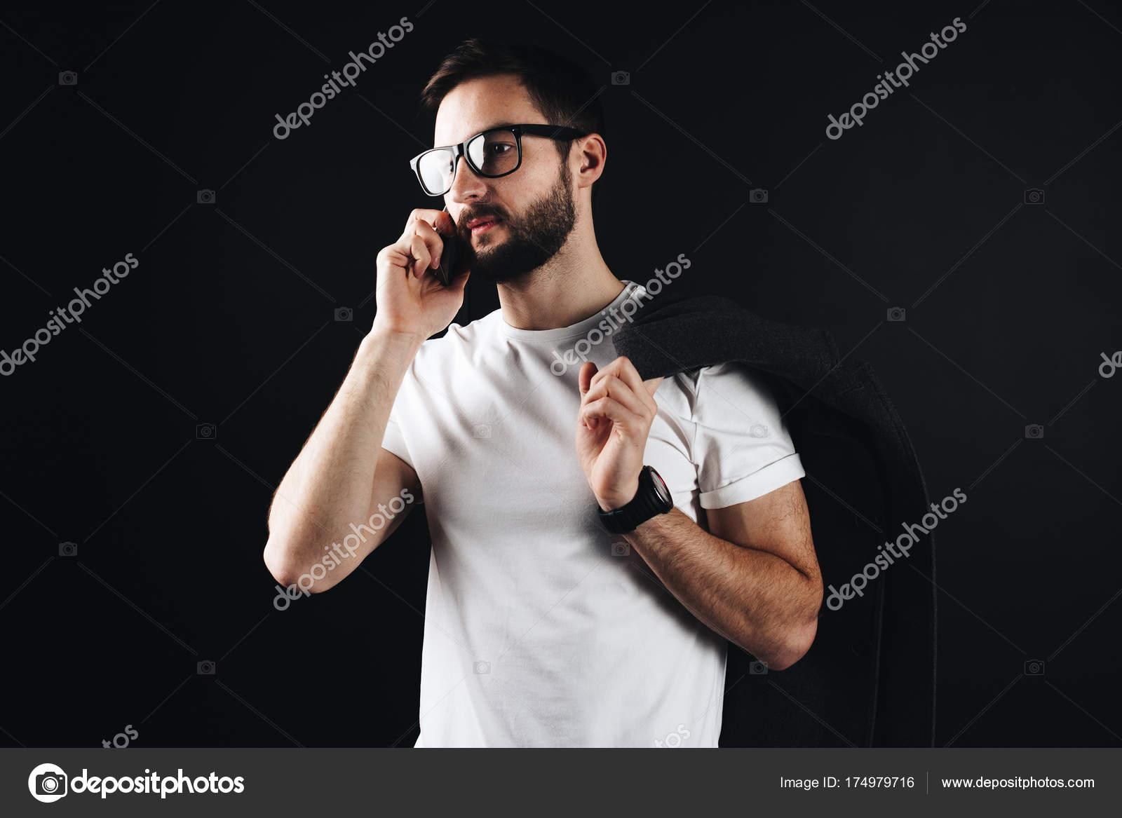 7807b3f6879e9 Joven pensativo había barbudo a empresario vistiendo blanco camiseta y  gafas. Hombre hablando por un teléfono inteligente y de pie en blanco camiseta  vacía ...