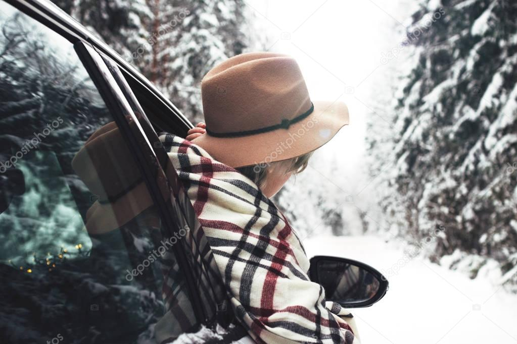 Boho woman traveling by white car and hanging out of the car window and look into the distance. Wearing hat and scarf.