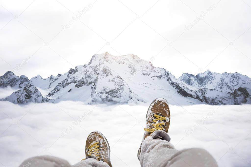 Traveler sitting on mountain peak, feet in hiking boots on background of rocky snowy landscape