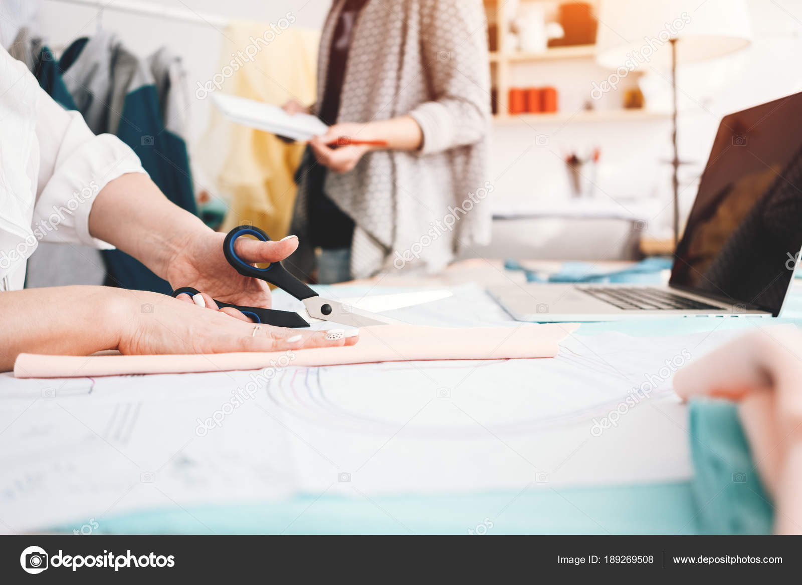 Two young clothing designer working fabric laptop sewing design