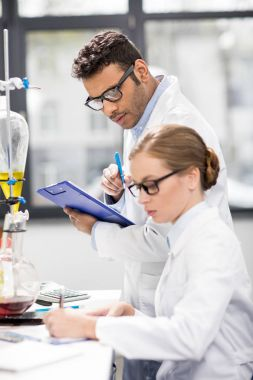 Side view of scientists working in laboratory stock vector