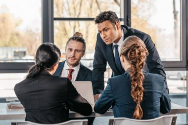 coworkers in formalwear arguing at business meeting