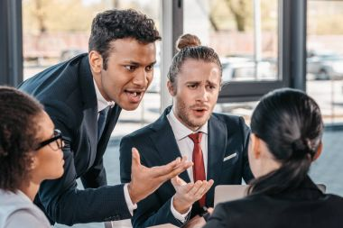 businesspeople arguing at meeting in office