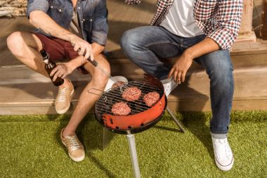 Cropped shot of young men sitting on porch and grilling burgers stock vector
