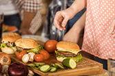 žena připravuje hamburgery na kuchyňské desce