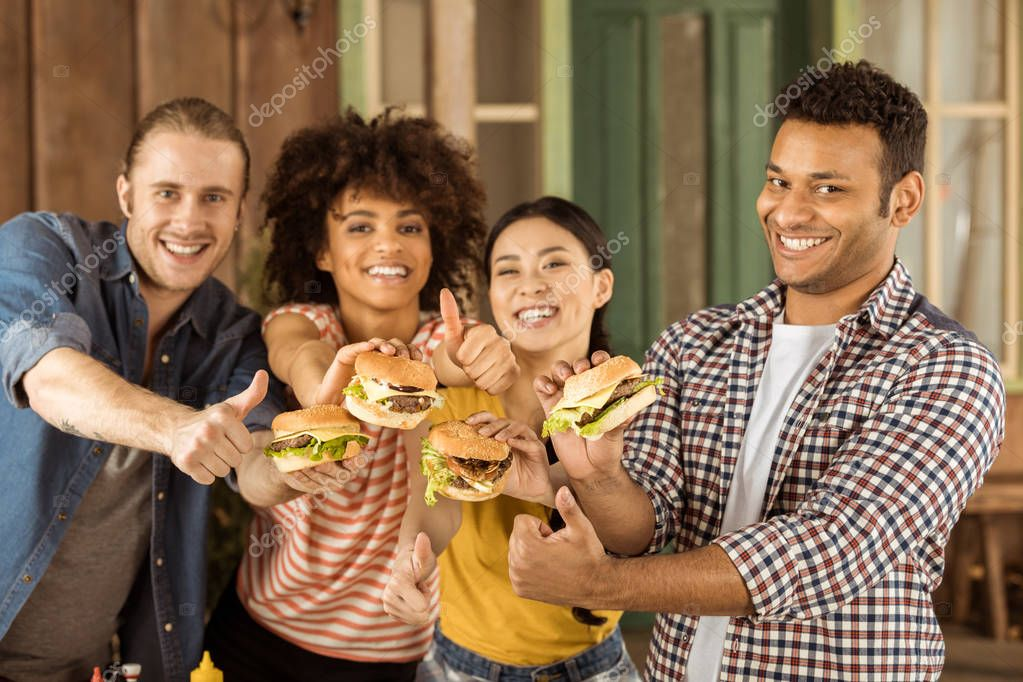 smiling multiethnic friends holding burgers