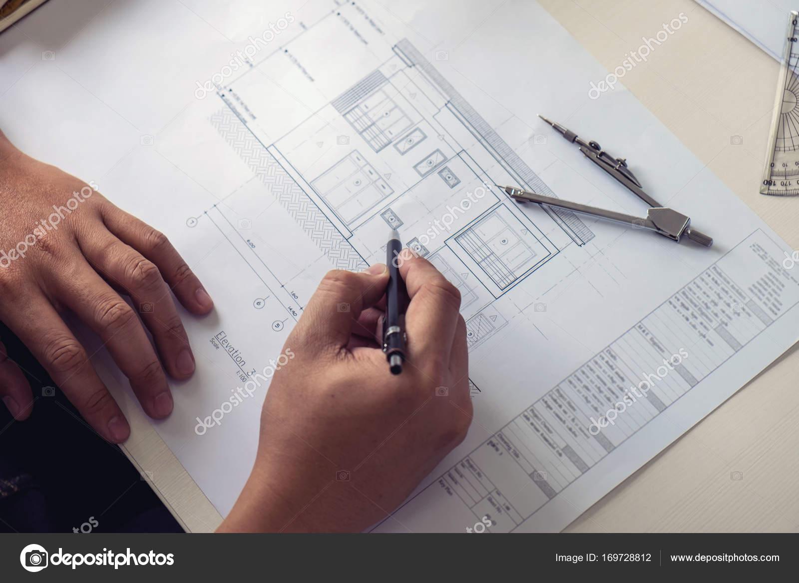 Architect working on blueprint engineer working with engineerin architect working on blueprint engineer working with engineerin stock photo malvernweather Images