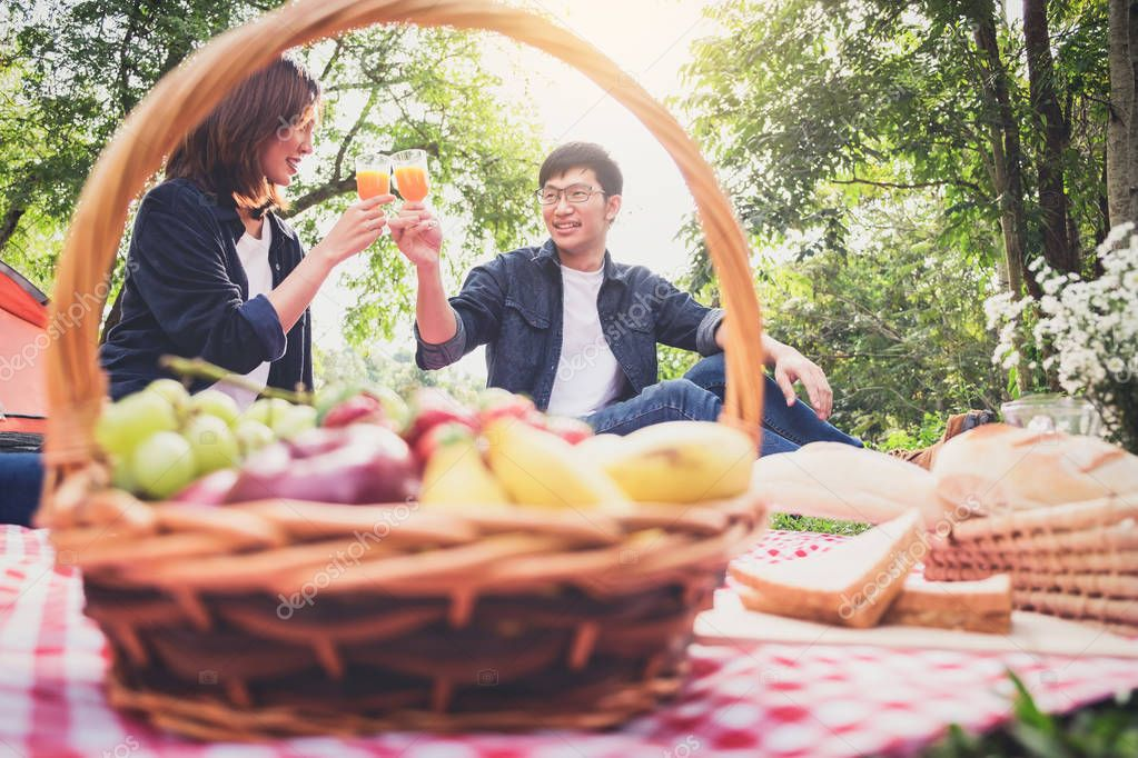 Couple in love drink a orange juice and fruits on summer picnic,
