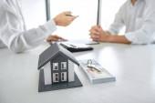 Realitní makléř prezentovat a konzultovat se zákazníkem k rozhodování podepsat pojistnou smlouvu, domácí model, týkající se nabídky hypotečních úvěrů pro a pojištění domu.