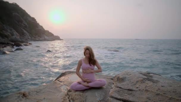 Těhotná žena cvičí jógu, stojí ve vrksasana pozici na pláži, na skalách. Ruce dívky v póze meditující. Ruce děvčete na břicho. Pozdrav slunci. Hatha jóga žena v růžovo-fialové teplákové soupravě.Žena s tetováním. Klidná dívka