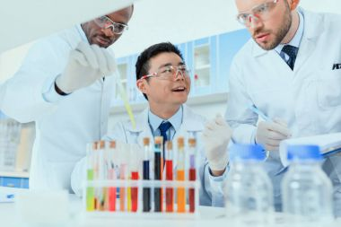 Professional scientists in white coats working together in chemical laboratory stock vector
