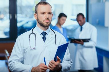 Confident doctor with folder