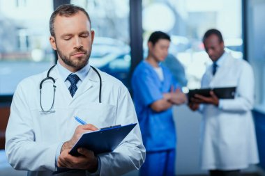 Portrait of confident doctor writing in folder in clinic with colleagues behind stock vector