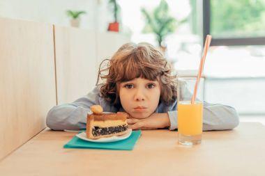 depressed little boy in cafe