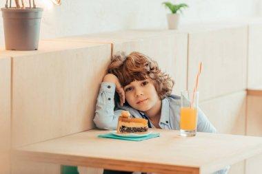 curly boy sitting in cafe