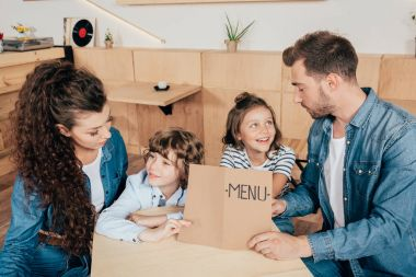 family with menu list in cafe