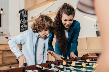 mother and son playing table footbal