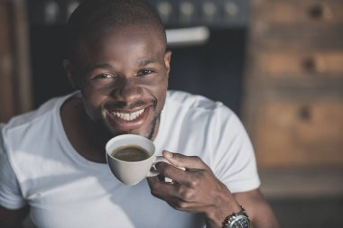 Handsome african american man having his morning coffee at home stock vector