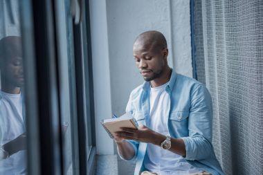 african american man making notes