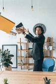 businessman throwing folders in office