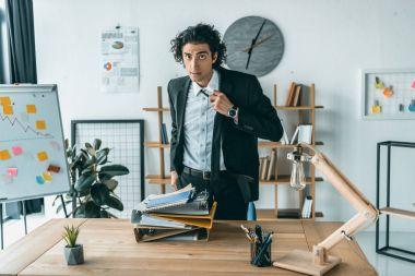 businessman tying necktie at workplace