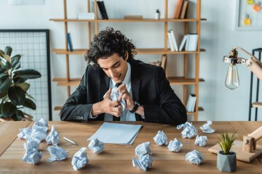 angry businessman crumpling papers at workplace