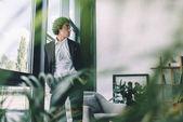 podnikatel, stojící u okna v úřadu