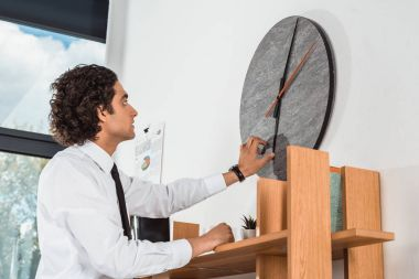 businessman setting time on clock in office