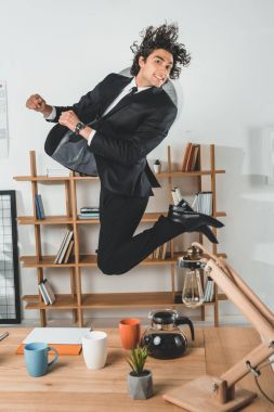 Businessman jumping in office