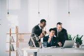 Fotografie businessmen looking at laptop screen
