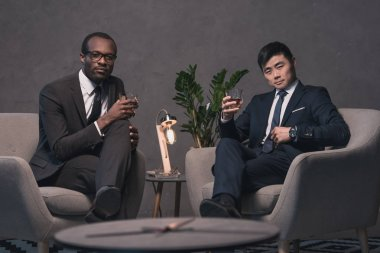 multiethic businessmen relaxing on armchairs
