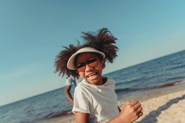 Adorable african american girl wearing sunglasses running on beach stock vector