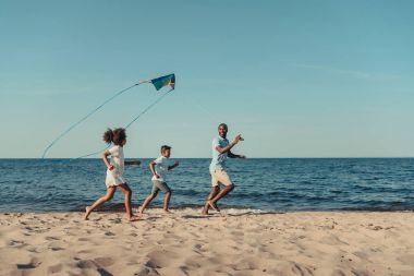 Father and kids playing with kite on beach