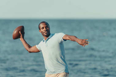 Handsome young african american man throwing rugby ball on beach stock vector