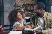 Fotografie Father and daughter reading book