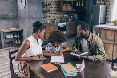 little girl writing at notebook with parents