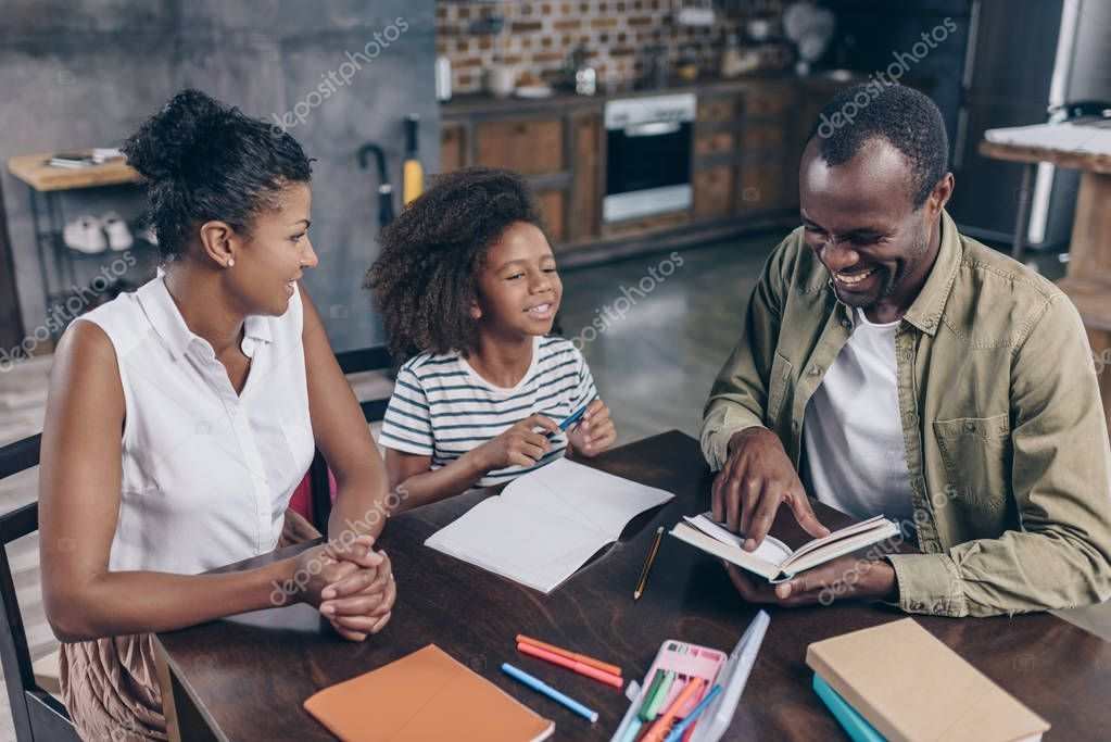 Girl and parents reading book together