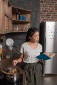 student, vaření a čtení knihy