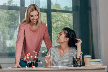 women studying with chemistry model