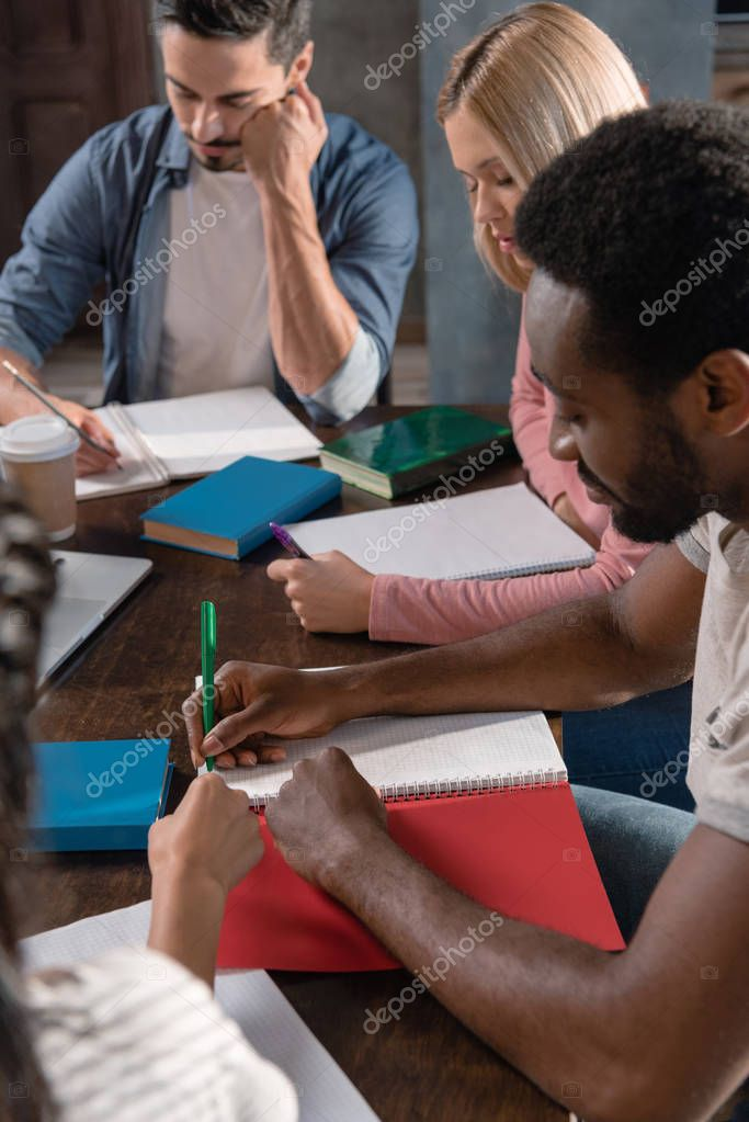 multiethnic students writing in copybooks