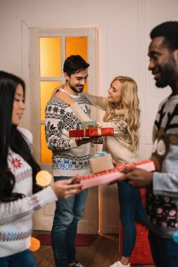 Multiethnic couples exchanging christmas gifts
