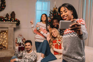 Multiethnic friends taking selfie on christmas