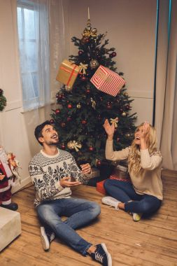 happy couple with gifts at home on christmas