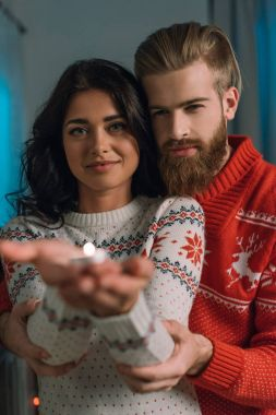 couple in christmas sweaters holding candle