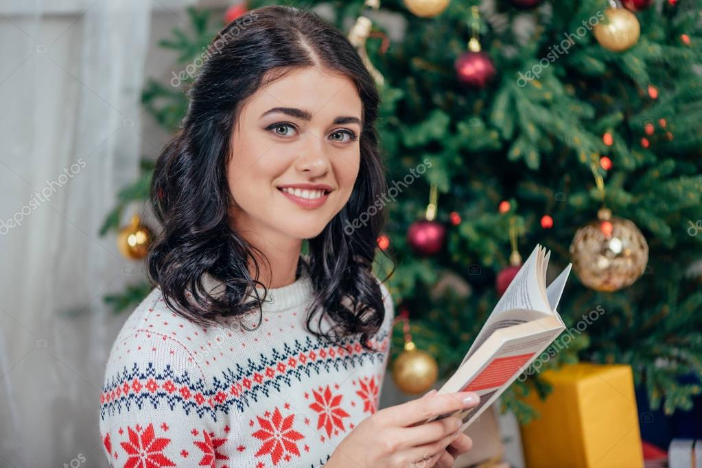 woman reading book on christmas
