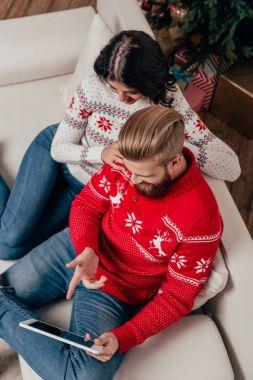 couple using tablet on christmas