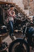 Fotografie muž v opravně s klasické motocykly